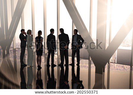 Composite image of business colleagues standing in large room overlooking city - stock photo