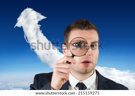 Composite image of businessman looking through magnifying glass against cloud arrow - stock photo