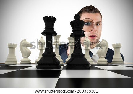 Composite image of businessman looking through magnifying glass with chessboard - stock photo