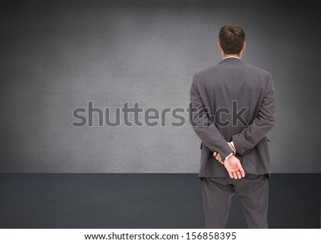 Composite image of businessman standing with hands behind back in grey room - stock photo