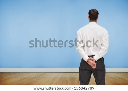 Composite image of businessman turning his back to camera looking at blue wall
