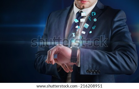 Composite image of businessman using hologram watch against futuristic glowing black background - stock photo