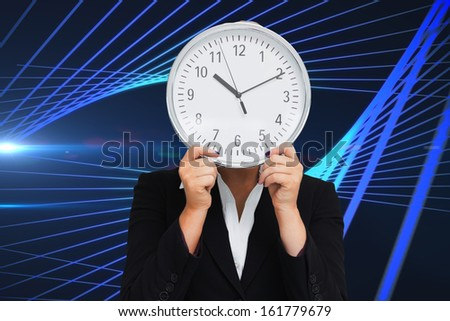 Composite image of businesswoman in suit holding a clock against white background - stock photo
