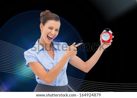 Composite image of businesswoman indicating alarm clock with finger - stock photo