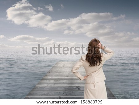 Composite image of businesswoman standing back to camera with hand on head on base in the ocean - stock photo