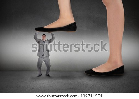 Composite image of businesswoman stepping on tiny businessman on grey background - stock photo