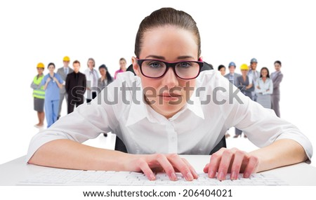 Composite image of businesswoman typing on a keyboard against group of workers - stock photo