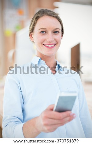 Composite image of businesswoman using her mobile phone - stock photo