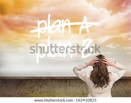 Composite image of businesswoman with hands on head standing back to camera  - stock photo