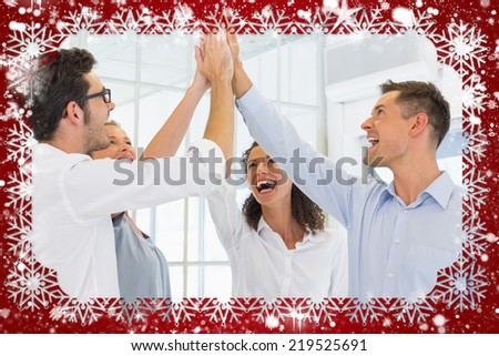 Composite image of casual business team high fiving against snow - stock photo