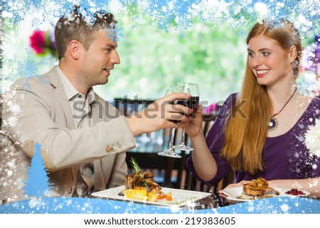 Composite image of cheerful couple having dinner together against snow - stock photo