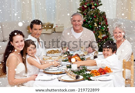 Composite image of Children pulling a Christmas cracker at home against snow falling - stock photo