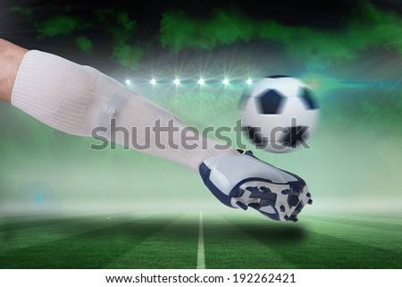 Composite image of close up of football player kicking ball against football pitch under green sky