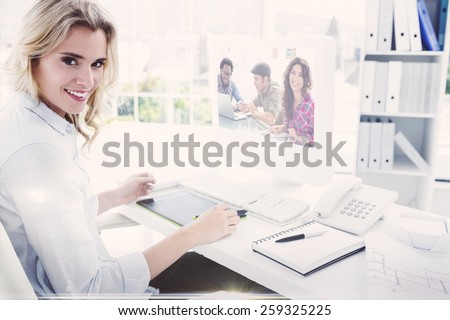 Composite image of creative team working together with one smiling at camera - stock photo
