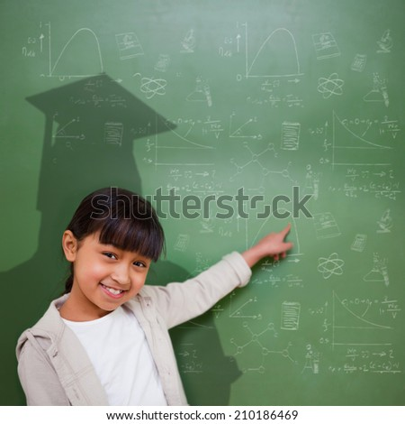 Composite image of cute pupil with graduate shadow in classroom - stock photo