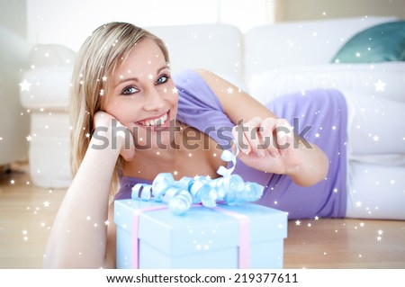 Composite image of Delighted blond woman holding a present lying on the floor against snow - stock photo