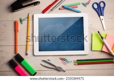Composite image of digital tablet on students desk showing clouds - stock photo