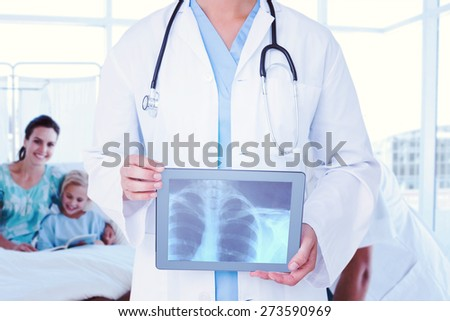 Composite image of doctor looking at xray on tablet - stock photo