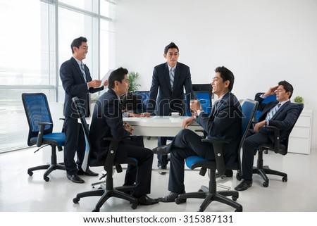 Composite image of entrepreneur having business meeting with his clones