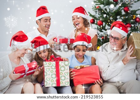 Composite image of Excited family exchanging gifts at christmas against snow falling - stock photo