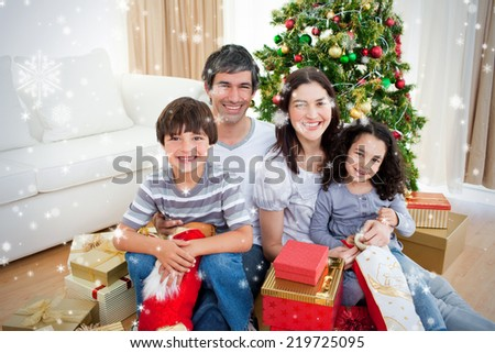 Composite image of Family Christmas portrait against snow falling - stock photo