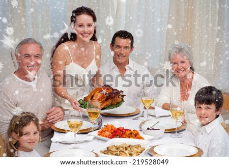Composite image of Family eating turkey in a dinner against snow - stock photo