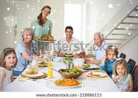 Composite image of Family having meal at dining table against snow falling - stock photo