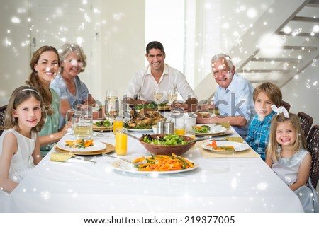 Composite image of Family having meal together at dining table against snow falling - stock photo