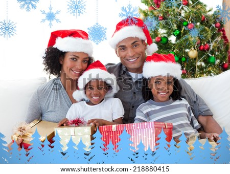 Composite image of family holding Christmas presents against snowflakes and fir trees in blue - stock photo