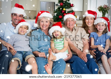 Composite image of Family in Santa hats celebrating Christmas against snow falling - stock photo
