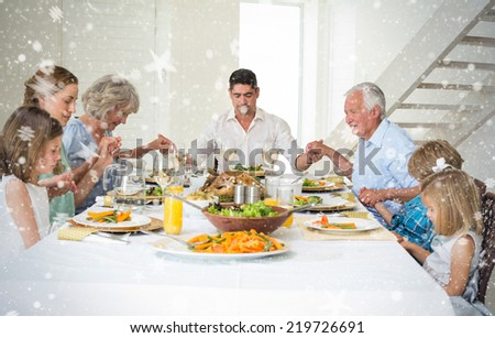 Composite image of Family praying together before meal at dining table against snow - stock photo