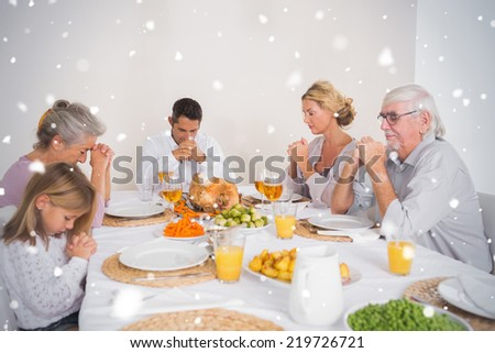 Composite image of Family saying grace before eating a turkey against snow falling - stock photo