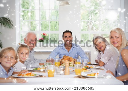 Composite image of Family smiling at thanksgiving against snow falling - stock photo