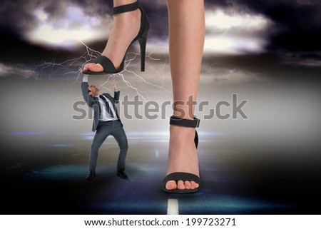Composite image of female feet in black sandals stepping on businessman against stormy sky over road with lightning - stock photo