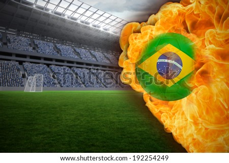 Composite image of fire surrounding brasil flag football against vast football stadium with fans in blue