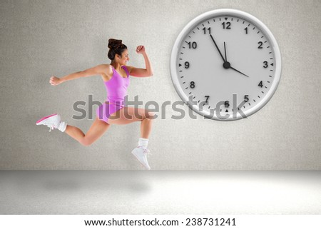 Composite image of fit brunette running against grey room - stock photo