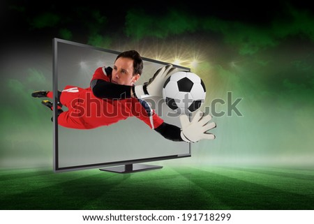 Composite image of fit goal keeper saving goal through tv against football pitch under green sky and spotlights - stock photo