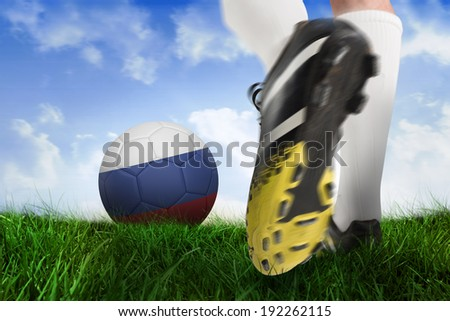 Composite image of football boot kicking russia ball against field of grass under blue sky