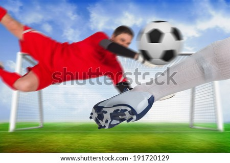 Composite image of football players tackling for the ball against football pitch and goal under blue sky - stock photo