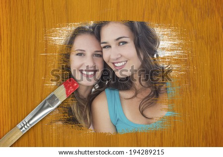 Composite image of friends smiling at camera with paintbrush dipped in red against wooden pine table - stock photo