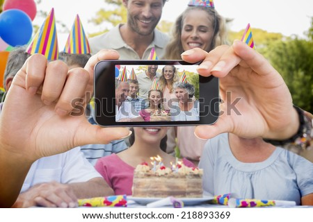 Composite image of hand holding smartphone showing photograph