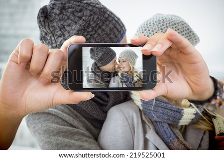 Composite image of hand holding smartphone showing photograph - stock photo