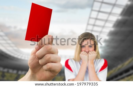 Composite image of hand holding up red card to fan against football stadium - stock photo