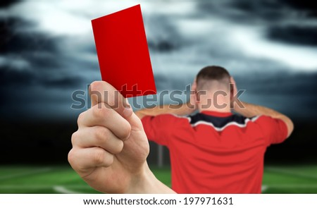 Composite image of hand holding up red card to player against football pitch under stormy sky - stock photo