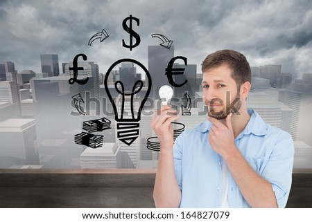Composite image of handsome model holding a bulb