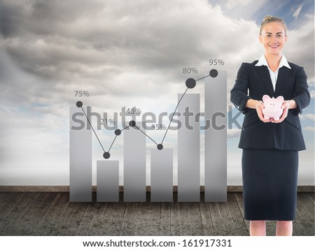 Composite image of happy blonde businesswoman holding a pink piggy bank
