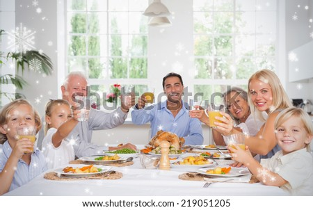 Composite image of Happy family toasting at thanksgiving dinner against snow falling - stock photo