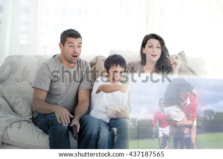 Composite image of happy family watching television on the sofa - stock photo