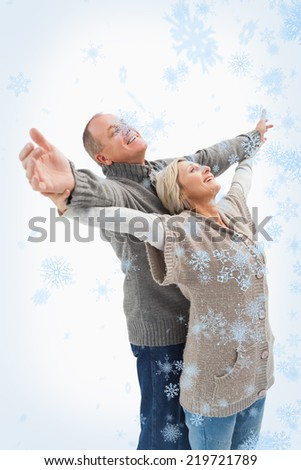Composite image of Happy mature couple in winter clothes with snow falling - stock photo