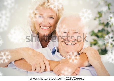Composite image of happy old couple portrait hugging against snowflakes - stock photo
